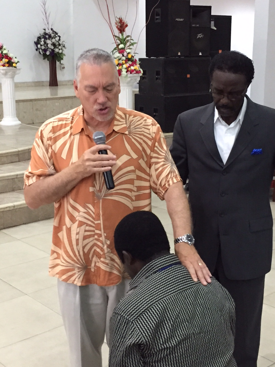 Man praying, another man standing over him with hand on shoulder
